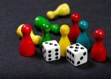 Figuras coloridas del juego con los dados a bordo imagen de archivo libre de regalías