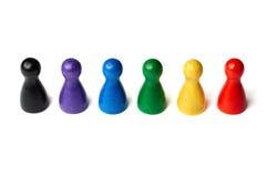 Figuras coloridas del juego que se colocan en una línea Trabajo en equipo del concepto, diversidad o colores del arco iris Foto de archivo