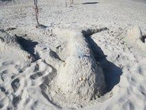 Figuras da areia e dos escudos na praia contra o mar imagem de stock