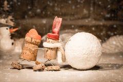 Figuras da cortiça do vinho, homens do conceito dois que rolam uma bola de neve fotos de stock