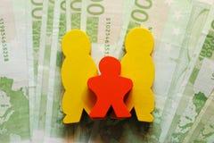 Figuras da família com euro cem do dinheiro fotografia de stock