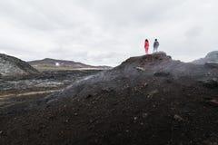 Figuras da mulher e do homem que estão no campo de lava do vulcão de Krafla em torno do pico de montanha de Leirhnjukur, Islândia fotos de stock
