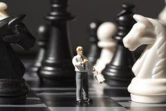 Figuras da peça do jogo de xadrez e da xadrez na placa do jogo Jogando a xadrez com a foto diminuta do macro da boneca Fotos de Stock