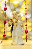 Figuras da porcelana do menino e da menina com grânulos do fundo imagens de stock