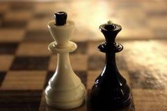 Figuras da xadrez do rei e da rainha no tabuleiro de xadrez Rei branco e rainha preta Conceito da competição e da estratégia foto de stock royalty free