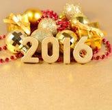 figuras de 2016 anos e decorações douradas do Natal Fotos de Stock