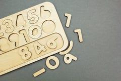 Figuras de 1 a 9 cortadas em uma placa de madeira e dispersadas sobre o fundo cinzento, espaço para o texto imagens de stock royalty free