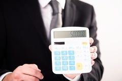 Figuras de la calculadora de la demostración del hombre de negocios foto de archivo