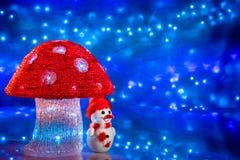 Figuras de la Navidad Muñeco de nieve debajo de una seta grande fotografía de archivo