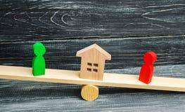 Figuras de madeira nas escalas esclarecimento da posse da casa, bens imobiliários corte rivais no negócio competição vencedor imagens de stock