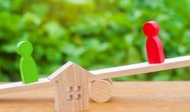 Figuras de madeira nas escalas esclarecimento da posse da casa, bens imobiliários rivais no negócio competição, corte propriedade imagens de stock