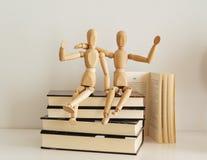 Figuras de madeira que comemoram a amizade no livros fechados, cultura bookday imagens de stock royalty free
