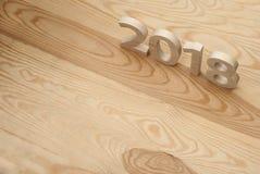 Figuras de madeira que formam 2018, cinzelado da madeira clara no backg Foto de Stock