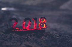 Figuras de madeira 2018 são queimadas em uma chama Fim conceptual da foto do ano imagem de stock