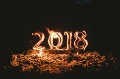 Figuras de madeira 2018 são queimadas em uma chama Fim conceptual da foto do ano fotos de stock