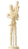Figuras de madera del niño que se sientan en las manos del padre Foto de archivo libre de regalías