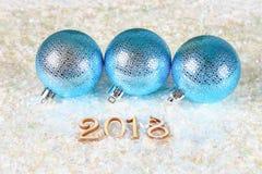 Figuras de madera de 2018 en nieve Atmósfera de la Navidad el Año Nuevo 2018 Bolas azules Imagen de archivo libre de regalías