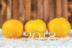Figuras de madera de 2018 en nieve Atmósfera de la Navidad el Año Nuevo 2018 mandarines Imagen de archivo