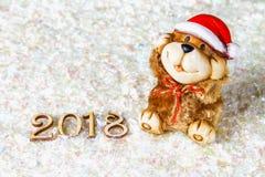 Figuras de madera de 2018 en nieve Atmósfera de la Navidad el Año Nuevo 2018 Un perro de juguete es un símbolo del Año Nuevo Fotografía de archivo libre de regalías