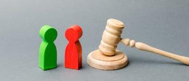 Figuras de madera de la gente que se coloca cerca del mazo del juez pleito Rivales de negocio Ley y justicia del conflicto de int fotografía de archivo