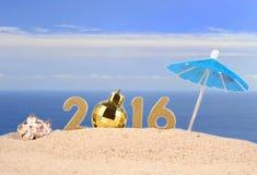 figuras de oro de 2016 años en una arena de la playa Foto de archivo