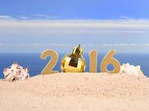 figuras de oro de 2016 años en una arena de la playa Foto de archivo libre de regalías