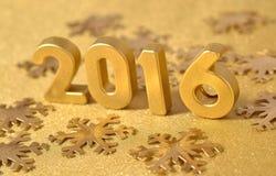 figuras de oro de 2016 años y copos de nieve de oro Imagenes de archivo