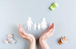 Figuras de papel de la familia en la adopción de concepto en maqueta gris de la opinión superior del fondo Imagenes de archivo