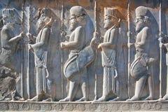 Figuras de soldados en trajes antiguos en el bajorrelieve de piedra destruido Foto de archivo