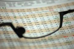 Figuras de um relatório financeiro através dos vidros de leitura Fotografia de Stock Royalty Free