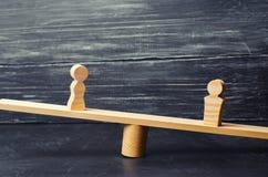 Figuras de un hombre y de una mujer en las escalas concepto de la desigualdad: el hombre y las mujeres en un pesaje equilibran, d Imagen de archivo libre de regalías