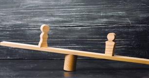Figuras de un hombre y de una mujer en las escalas concepto de la desigualdad: el hombre y las mujeres en un pesaje equilibran, d Imagen de archivo