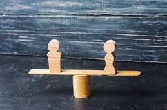 Figuras de un hombre y de una mujer en las escalas concepto de la desigualdad: el hombre y las mujeres en un pesaje equilibran, d Imágenes de archivo libres de regalías