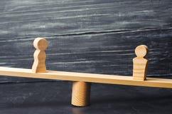 Figuras de un hombre y de una mujer en las escalas concepto de la desigualdad: el hombre y las mujeres en un pesaje equilibran, d Fotografía de archivo