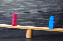 Figuras de un hombre y de una mujer en las escalas concepto de la desigualdad: el hombre y las mujeres en un pesaje equilibran, d Foto de archivo libre de regalías