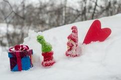Figuras de un muchacho y una muchacha en el invierno, una estatuilla del corazón y una caja de regalo, un día del ` s de la tarje Fotos de archivo