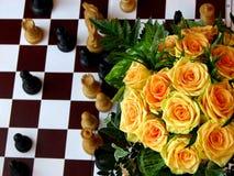Figuras del ajedrez con las rosas imagen de archivo libre de regalías