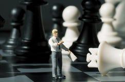 Figuras del hombre de negocios y del ajedrez en tablero del juego Jugar a ajedrez con la foto miniatura de la macro de la muñeca Fotos de archivo libres de regalías