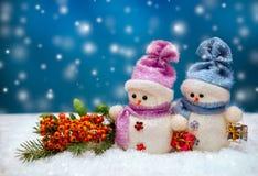 Figuras del muñeco de nieve con los copos de nieve en fondo de la Navidad Imagen de archivo libre de regalías
