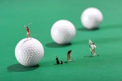 Figuras diminutas dos jogadores de golfe que jogam o golfe Fotos de Stock