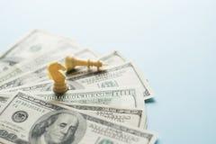 Figuras do jogo de xadrez e dólares americanos no fundo azul com foco seletivo, planejar da estratégia empresarial Sucesso fotografia de stock royalty free