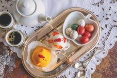 Figuras do maçapão sob a forma das galinhas brancas e amarelas na tabela da Páscoa com copos de café e ovos da pastelaria em um b Imagem de Stock Royalty Free