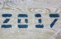 Figuras 2017 dos grânulos de vidro no fundo de madeira branco, Imagens de Stock