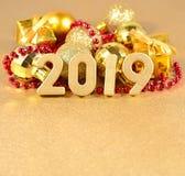 figuras douradas de 2019 anos no fundo do decorati do Natal Fotografia de Stock