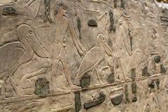 Figuras e hieróglifos egípcios na pedra Foto de Stock