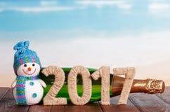 Figuras en 2017, muñeco de nieve, champán de la botella en la tabla contra el mar Fotos de archivo