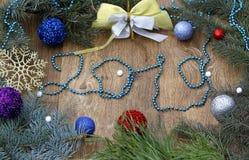 Figuras 2019 feitas de grânulos azuis, de decorações do Natal com uma árvore, de bolas do Natal e de curva em um fundo escuro fotografia de stock