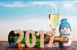 Figuras garrafa 2017 do champanhe e vidro, boneco de neve, presentes contra o mar Imagem de Stock