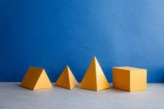 Figuras geométricas abstractas Objetos rectangulares de la pirámide del cubo tridimensional del tetraedro en fondo del gris azul Imagenes de archivo
