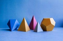 Figuras geométricas abstratas Objetos retangulares do cubo tridimensional do tetraedro da pirâmide do dodecahedron no azul fotografia de stock